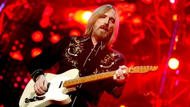 Ein Mann vor rotem Hintergrund mit Gitarre.