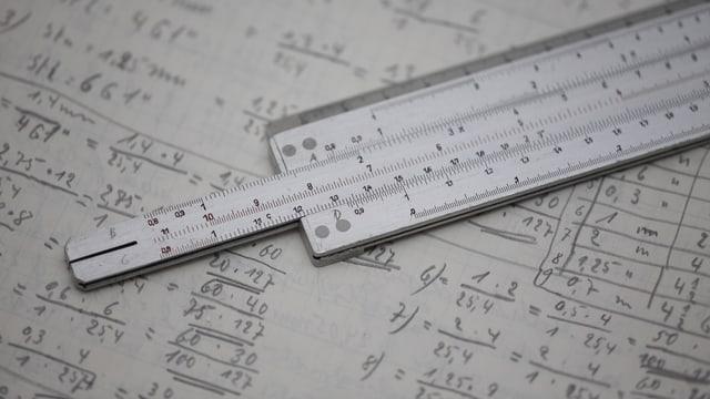 Ein Blatt Papier mit vielen, kleinen Zahlen und einem Rechenschieber.