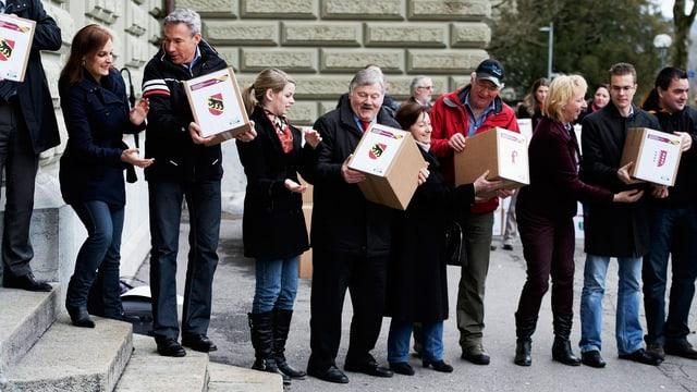 Schlange mit Menschen am Bundeshaus mit Kartons voll Unterschriften.