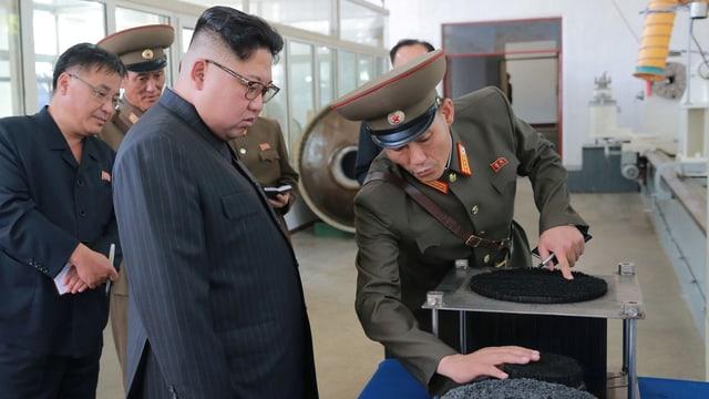 Kim lässt sich von einem uniformierten Militär etwas vorführen.