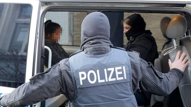 Die Polizei verhaftet eine verdächtige Frau während der grossangelegten Razzien in Deutschland. (keystone)