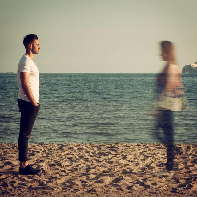 Ein Paar steht am Strand. Die Frau verschwimmt.