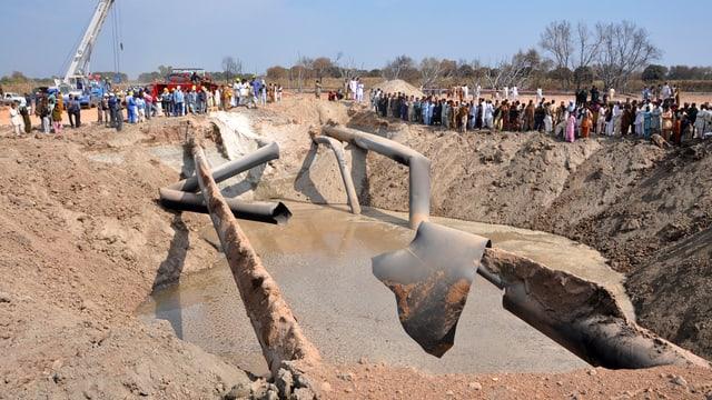 Arbeiter und Schaulustige stehen um zestörte Pipelines.