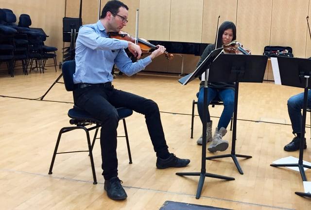Zwei Männer und eine Frau in einem grossen Raum. Sie spielen auf ihren Geigen und Bratschen.