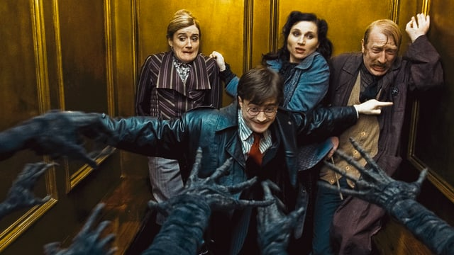 Ein junger Mann beschützt zwei Frauen und einen Mann vor schwarzen Händen, welche in das Bild greifen.