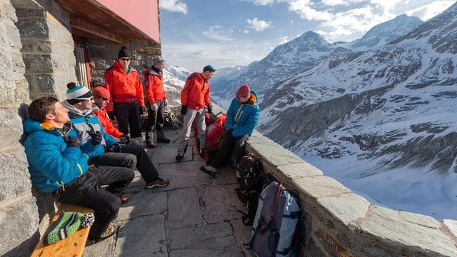Menschen an einer Hütte vor einem Bergpanorama