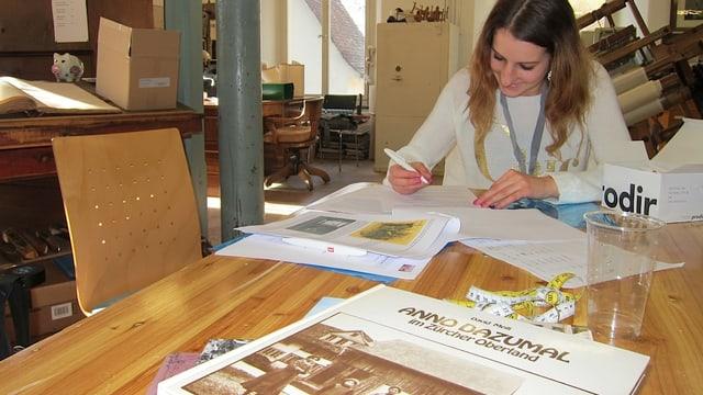 Mädchen schreibt am Tisch, Buch im Vordergrund