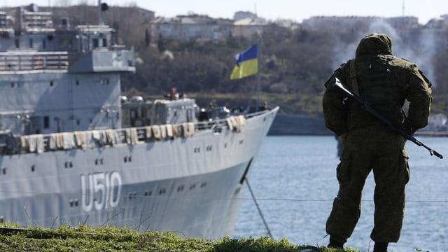 Ein Soldat steht beim Hafen mit Blick auf ein Kriegsschiff.