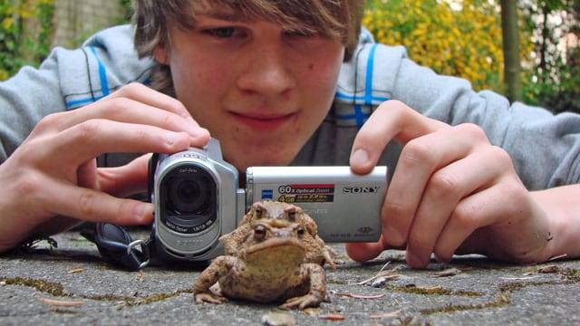 Jugendlicher mit Videokamera filmt ein Erdkrötenpaar vor ihm