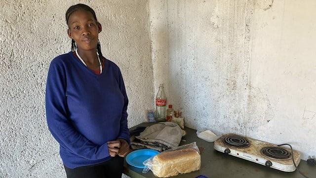 Eine schwarze Frau steht in ihrer Kochnische.