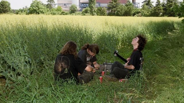 Drei Heavy-Metal-Fans mit Gitarre im Kornfeld