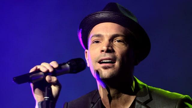 Roger Cicero mit Hut und Mikrofon auf einer Bühne.