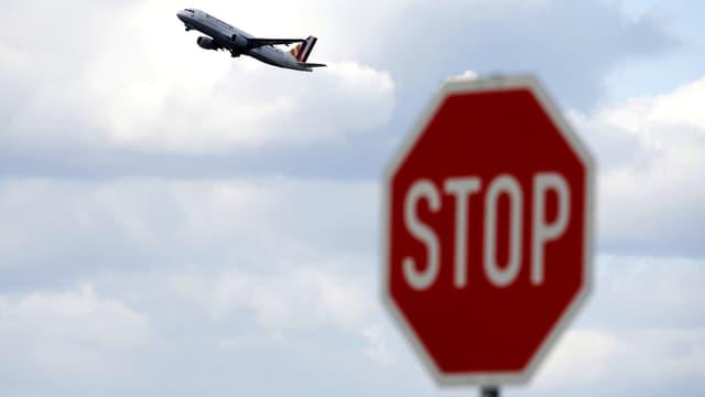 Ein Stoppschild im Vordergrund. Im Bildhintergrund sieht man eine Germanwings-Maschine steil in den Himmel über Düsseldorf steigen.
