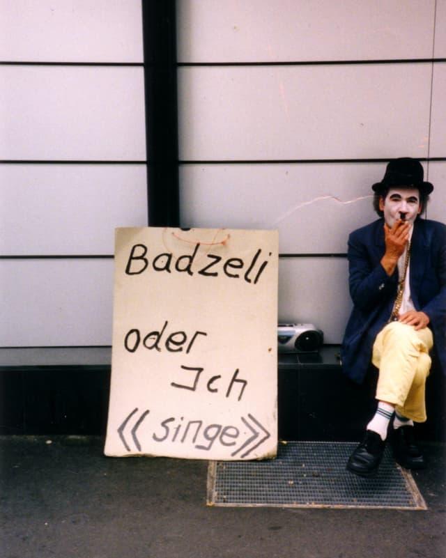 Ein Mann mit Charlie-Chaplin-Verkleidung sitzt neben einem Karton mit der Aufschrift «Badzeli oder ich ‹singe›»