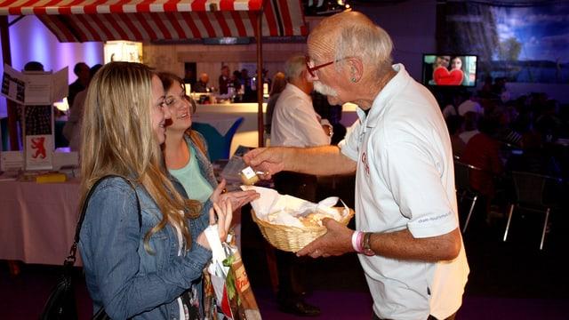 Ein Mann verteilt Biberli an zwei junge Frauen.