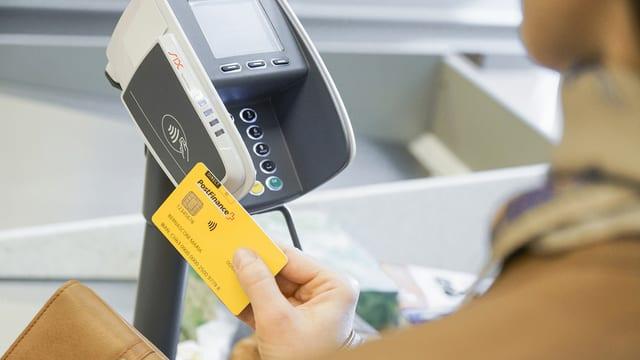 Hand am mit Postcard am Bezahlterminal.