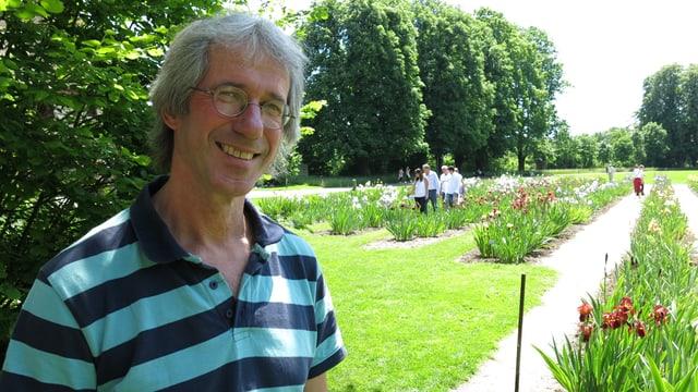 Ein Mann steht vor einer Blumenwiese