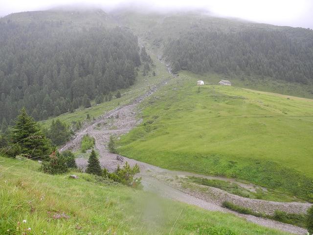 Blick über wolkenverhangenes Tal mit wildem Fluss.