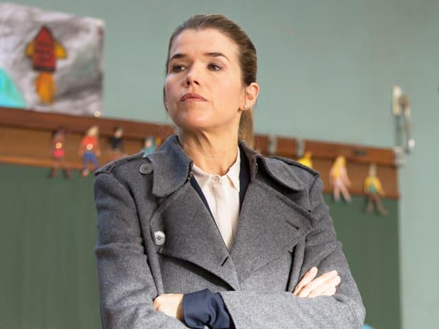 Eine Frau in grauem Mantel blickt streng auf die Seite.