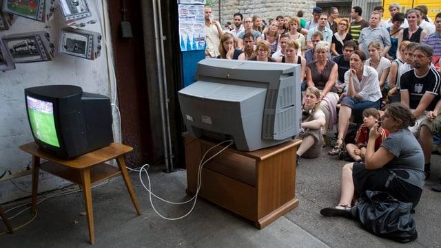 Zwei kleine Fernseher stehen in Freien, mehrere Personen sitzen davor.