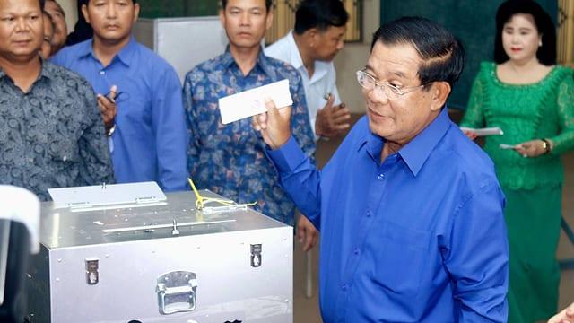 Mann in blauem Hemd und Brille steht vor Wahlurne, Personen rundum schauen ihm zu.