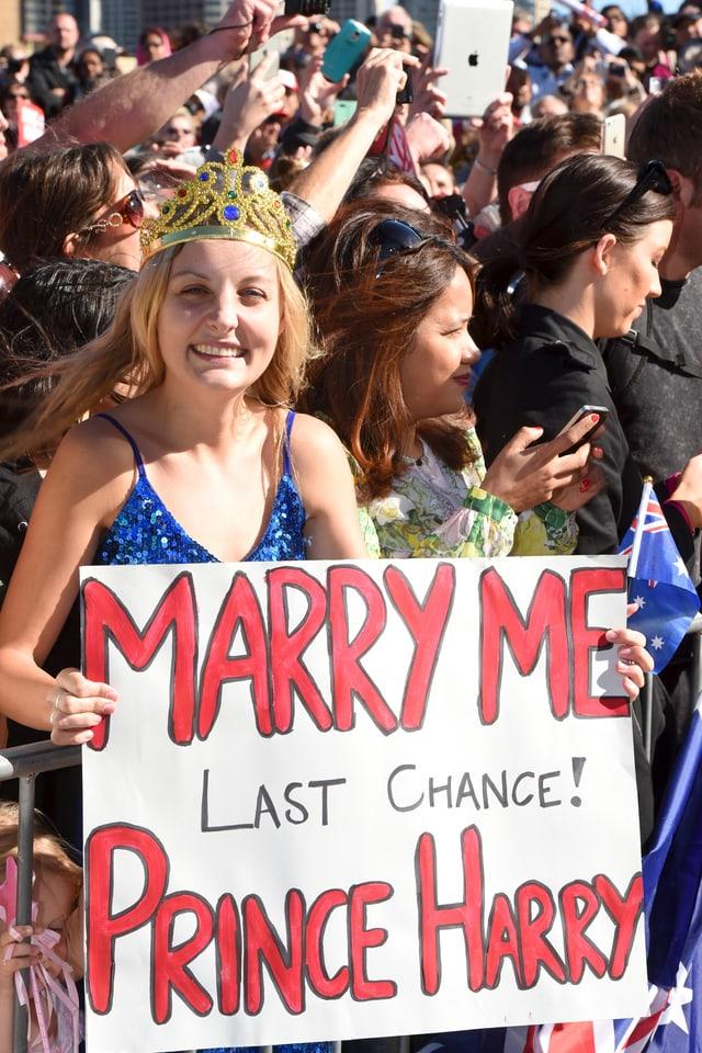 Eine Frau trägt ein Pappschild auf dem sie Prinz Harry auffordert, sie zu heriaten.