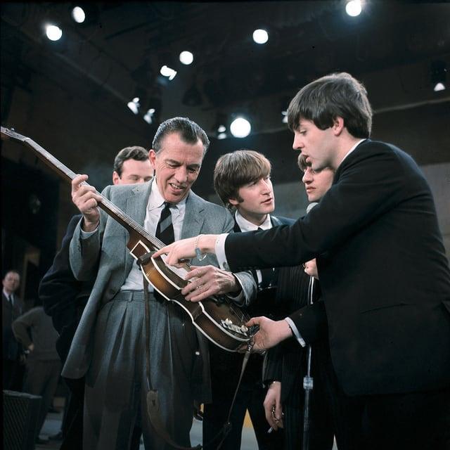 Der TV-Entertainer Es Sullivan hält eine Gitarre, Paul McCartney von den Beatles steht neben ihm.