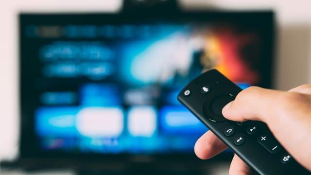 Eine Hand hält eine Fernsehfernbedienung. Im Hintergrund ist ein Fernsehgerät zu sehen