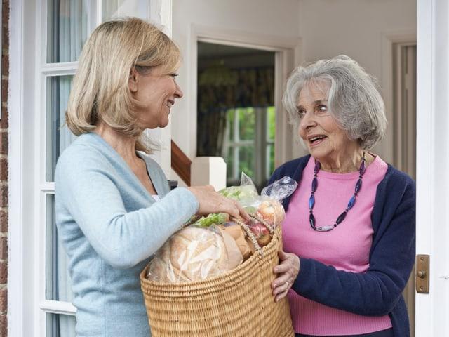 eine Frau übergibt einer Seniorin eine Tasche mit Einkäufen.