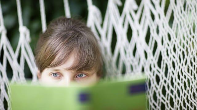 Eine Frau liest ein Buch in einer Hängematte.