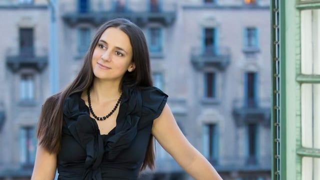Eine junge Frau mit schwarzen langen Haaren mit schwarzem Oberteil und schwarzer Kette lächelt.