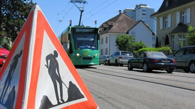 Im Vordergrund steht ein Baustellendreieck, im Hintergrund sieht man ein BVB-Tram anfahren.