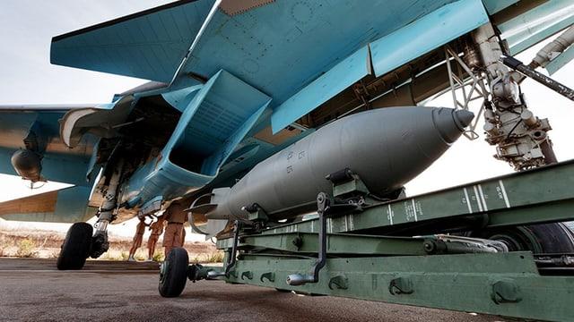 Eine Bombe wird unter den Flügel eines russischen Kafflugzeugs geschoben.