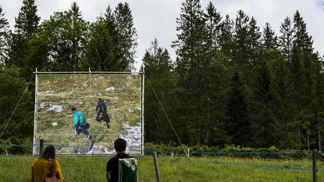 Zwei Menschen betrachten eine Fotografie, auf der zwei Menschen in der Natur zu erkennen sind.