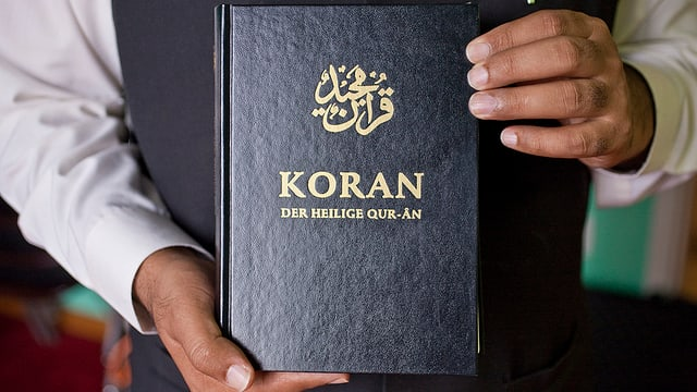 Zwei Hände halten einen Koran