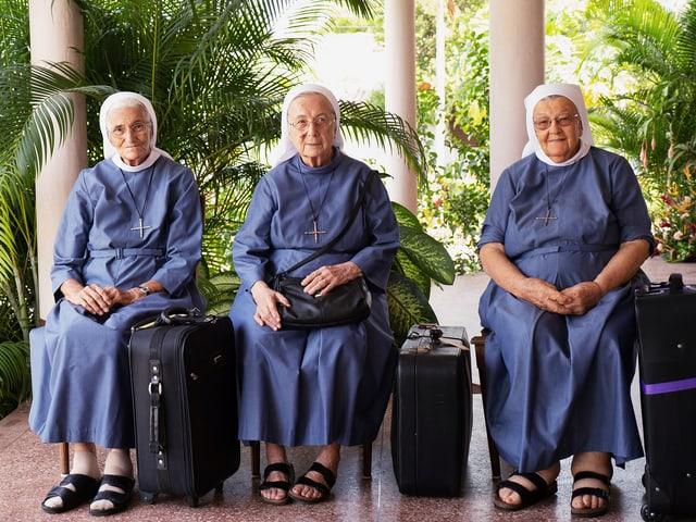 3 Ordensschwestern mit Koffern.