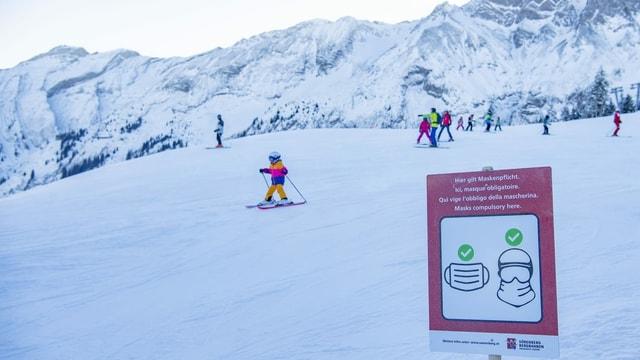 Kind fährt Ski vor Schild, auf dem die Maskenpflicht visualisiert ist.
