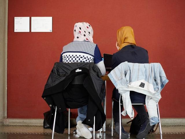 Zwei Frauen mit Kopftuch an einem Pult. Man sieht sie von hinten.