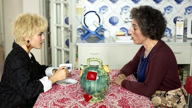 Zwei Frauen sitzen sich an einem Küchentisch gegenüber: die eine ist jung und trägt kurzes Haar, die andere hat einen Lockenkopf und eine markante Nase.