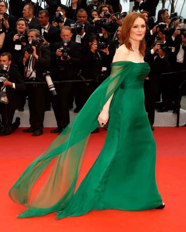 Frau in grünem Kleid auf rotem Teppich