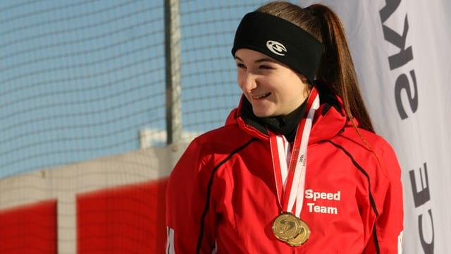 Eine Frau strahlt mit zwei Medaillen.