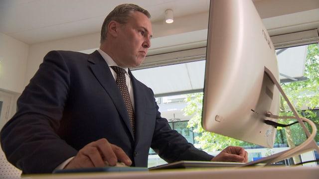 Mann im Anzug arbeitet am Computer.