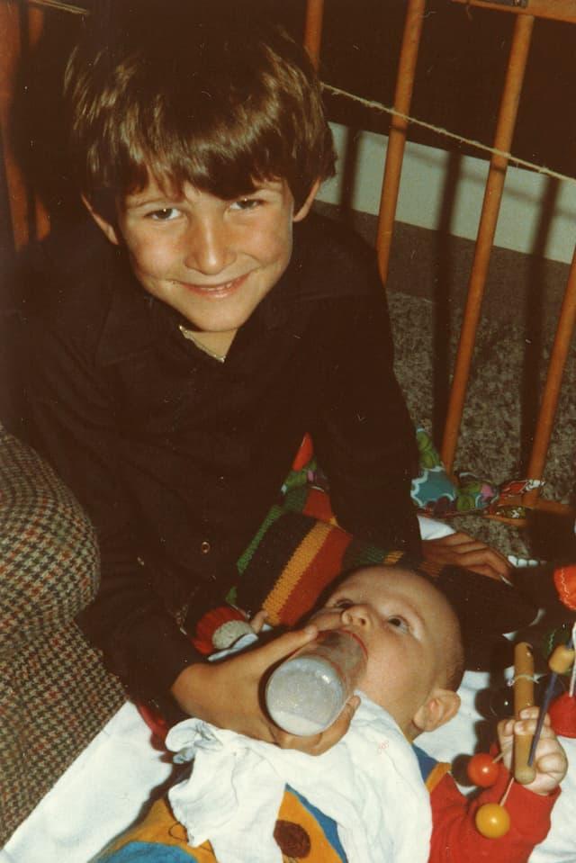 Ein dunkelhaariger Bub sitzt am Boden und gibt einem Baby die Trinkflasche.