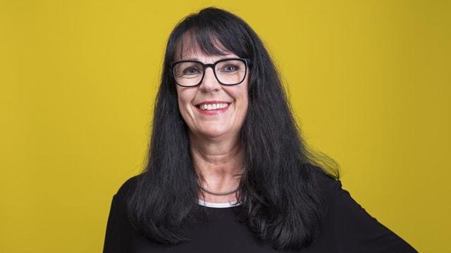 Eine Frau mit langen schwarzen Haaren und Brille
