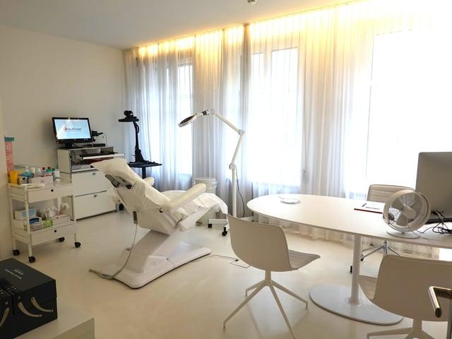 Behandlungszimmer mit Behandlungsstuhl, Geräten und Schreibtisch.
