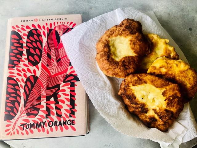 Neben dem Roman «Dort Dort» von Tommy Orange steht ein Teller mit selbstgemachtem Fry Bread.