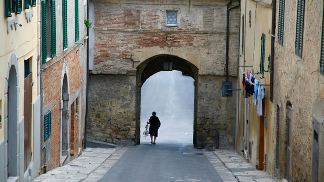 leere italienische Strasse, alte Frau geht mit Blumen durch ein Tor