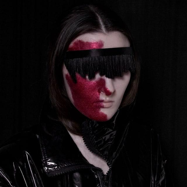 Vor schwarzem Hintergrund ist ein Model abgebildet, deren Gesicht mit einem roten Glitzermake-up und einem Band über den Augen versteckt wird.