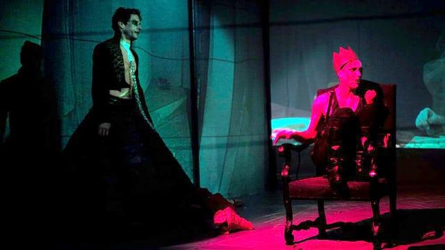 Auf einer Bühne steht eine Person in langem Mantel neben einer gekrönten Person auf einem Thron.