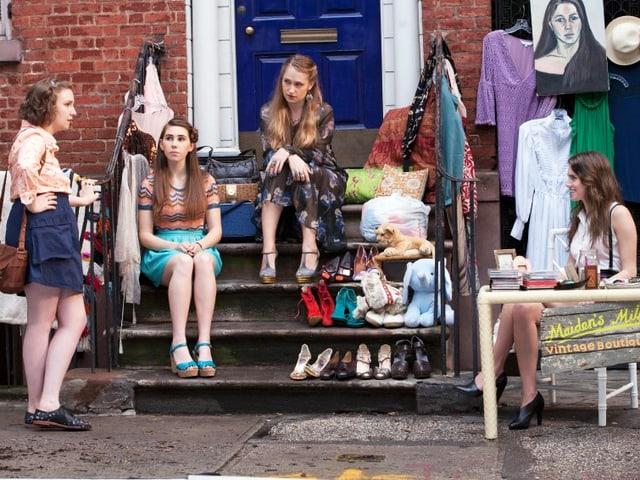 Die Girls sitzen vor einer Haustür, wo sie einen Trödelmarkt veranstalten.